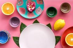 Modello vuoto del piatto Tazze e piatti vicino alle foglie tropicali e frutti sulla vista superiore del fondo rosa Immagine Stock Libera da Diritti