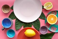 Modello vuoto del piatto Tazze e piatti vicino alle foglie tropicali e frutti sulla vista superiore del fondo rosa Fotografie Stock