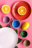 Modello vuoto del piatto Tazze e piatti vicino alle foglie tropicali e frutti sulla vista superiore del fondo rosa Immagini Stock