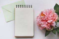 Modellphotographie mit rosa Pfingstrose, Notizbuch und Umschlag Stockfotos