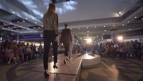 Modellpodiet i höga häl går på Catwalk till modeshowen av kvinnlig kläder för den märkes- samlingen arkivfilmer