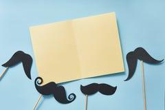 Modellsvartmustascher på blå pappers- bästa sikt för bakgrund Lyckligt kort för hälsning för faderdag med det gula arket av pappe arkivfoton
