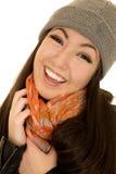 Modelo adolescente americano bastante asiático que sonríe llevando una gorrita tejida y una a Imagen de archivo libre de regalías