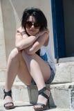 Modelo adolescente con las gafas de sol que se sientan en las escaleras Imagenes de archivo