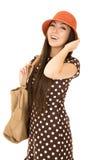 Modelo adolescente confiado de la muchacha que lleva un sombrero anaranjado w del vestido del lunar Fotos de archivo libres de regalías