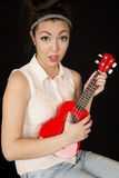Modelo adolescente de la muchacha que juega un ukelele con una expresión facial de la diversión Foto de archivo libre de regalías
