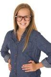 Modelo adolescente en la sonrisa de la camisa y de los vidrios del dril de algodón Foto de archivo