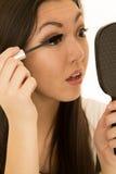 Modelo adolescente hermoso que aplica el rimel que sostiene el espejo de mano Imagenes de archivo