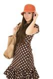 Modelo adolescente lindo de la muchacha que lleva un vestido del lunar y un sombrero anaranjado Imagenes de archivo