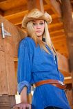 Modelo adolescente rubio con el vaquero Hat en el granero de madera Fotografía de archivo