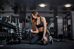 Modelo adulto joven de la muchacha que hace levantamiento de pesas en el gimnasio que se sienta cerca del espejo imagen de archivo
