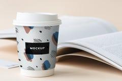 Modelo afastado do copo de café em uma tabela com um livro aberto imagens de stock