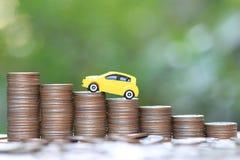 Modelo amarelo diminuto do carro na pilha crescente de dinheiro das moedas no fundo do verde da natureza, de dinheiro de salvamen fotografia de stock