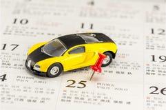 Modelo amarelo do carro e um percevejo vermelho no calendário chinês fotografia de stock royalty free