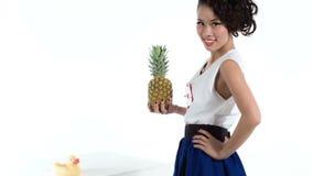 Modelo asiático alegre com o abacaxi e o pato amarelo que levantam no estúdio filme
