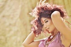 Modelo asiático con maquillaje en cara en vestido del feulette contra fondo del pajar foto de archivo