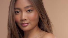 Modelo asiático tailandés con maquillaje natural en fondo beige almacen de video