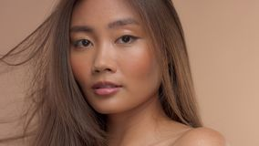 Modelo asiático tailandés con maquillaje natural en fondo beige almacen de metraje de vídeo