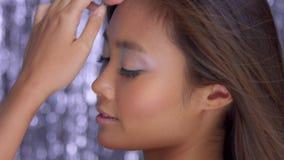 Modelo asiático tailandés en estudio con el fondo del disco de la lluvia y el maquillaje de plata del partido almacen de video