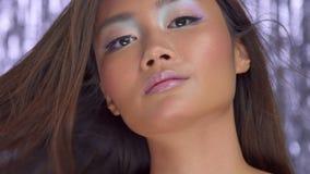 Modelo asiático tailandés en estudio con el fondo del disco de la lluvia y el maquillaje de plata del partido almacen de metraje de vídeo