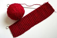Modelo asociado del rojo de los rayos Una bola de lanas y de agujas que hacen punto imagen de archivo