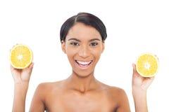 Modelo atractivo alegre que lleva a cabo rebanadas de naranja en ambas manos Foto de archivo