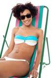 Modelo atractivo del bikini asentado en un deckchair Foto de archivo libre de regalías