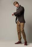 Modelo atractivo en chaqueta y zapatillas de deporte marrones fotografía de archivo