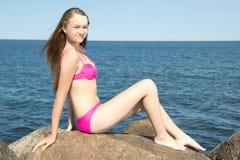 Modelo atractivo en el bikini rosado que se sienta en piedra en la playa rocosa Foto de archivo libre de regalías