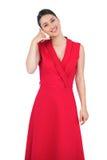 Modelo atractivo en el vestido rojo que hace gesto de la llamada de teléfono Imagenes de archivo