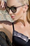 Modelo atractivo hermoso de la chica joven de la mujer del pelo rubio en gafas de sol y traje de baño negro elegante con los cris imágenes de archivo libres de regalías