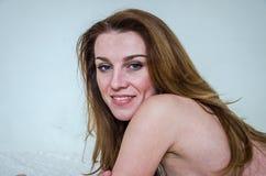 Modelo atractivo hermoso joven de la muchacha con una mentira atractiva de la sonrisa hermosa y del pelo largo en la cama con los Imágenes de archivo libres de regalías