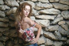 Modelo atractivo joven que presenta cerca de la pared resistida vieja Fotos de archivo libres de regalías