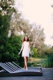 Modelo atractivo sonriente de pelo largo encantador de la muchacha morena feliz en un paseo blanco del vestido por el río foto de archivo libre de regalías