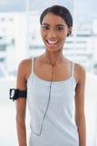 Modelo atractivo sonriente en la ropa de deportes que escucha la música Imágenes de archivo libres de regalías