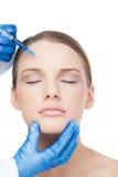 Modelo atrativo relaxado tendo a injeção do botox na testa imagens de stock