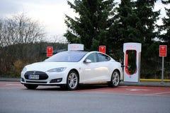 Modelo blanco S de Tesla que es cargado en la estación del sobrealimentador Imágenes de archivo libres de regalías