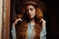 Modelo blando del pelirrojo con los ojos cerrados en el sombrero de paja que presenta en pas Fotografía de archivo