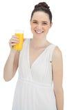 Modelo bonito alegre en el vestido blanco que sostiene el vidrio de zumo de naranja Fotografía de archivo