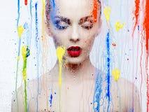 Modelo bonito através do vidro com cores brilhantes Foto de Stock Royalty Free