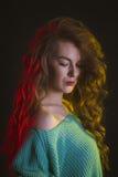 Modelo bonito com cabelo encaracolado na luz da cor Imagem de Stock
