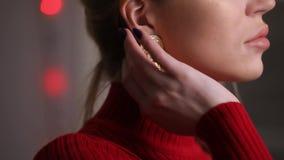 Modelo bonito da forma no vestido vermelho que levanta tocando em brincos, conceito da joia filme