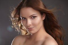 Modelo bonito da jovem mulher com voo do cabelo marrom Beleza com pele limpa, composição da forma Compõe, penteado encaracolado Imagem de Stock