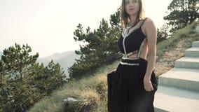 Modelo bonito da jovem mulher em um vestido longo elegante macio preto que levanta na câmera no fundo de uma montanha vídeos de arquivo
