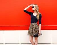 Modelo bonito da mulher da forma na saia e nos óculos de sol do leopardo foto de stock