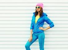 Modelo bonito de la mujer de la moda del retrato en la ropa colorida que presenta sobre el fondo blanco las gafas de sol rosadas  Fotos de archivo