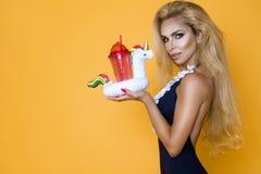 Modelo bonito em um biquini e em óculos de sol, guardando uma bebida e um flamingo cor-de-rosa inflável foto de stock royalty free