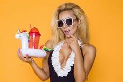 Modelo bonito em um biquini e em óculos de sol, guardando uma bebida e um flamingo cor-de-rosa inflável fotos de stock