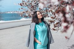 Modelo bonito no vestido azul e no revestimento cinzento pela árvore de florescência da mola fotos de stock royalty free