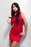 Modelo bonito no vestido vermelho no fundo cinzento Imagens de Stock